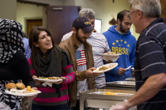 Visitors are served food during an interfaith Thanksgiving meal at Heartsong