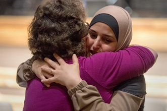 Barbara Watt (left) and Ayaat Alomari embrace during an interfaith Thanksgiving meal at Heartsong United Methodist Church