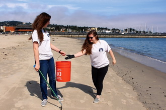 Shelby O'Neil, right, and a friend help clean up a beach in California.